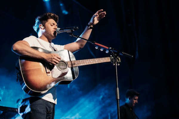 Niall Horan playng with a guitar live