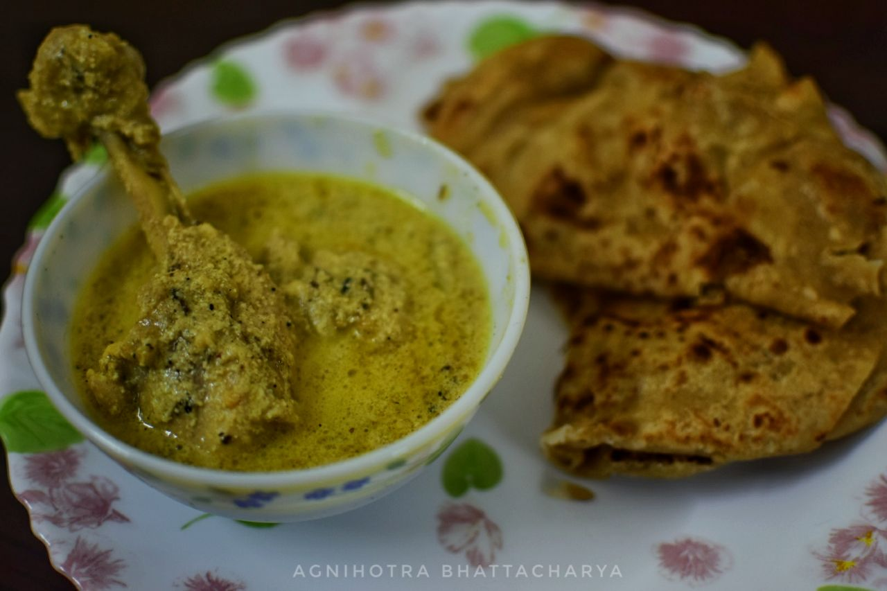 Picture of paratha with chicken in white curry.