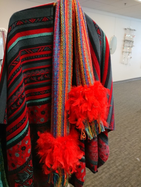 reds scarf with feathers over matching poncho