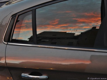 A Roma sunset trapped in a car.