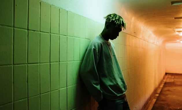 man in gray dress shirt standing beside green wall