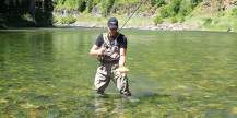 This photo shows a fly fisherman standing in a river with a trout while wearing the Orvis Silver Sonic Convertible-Top Waders.