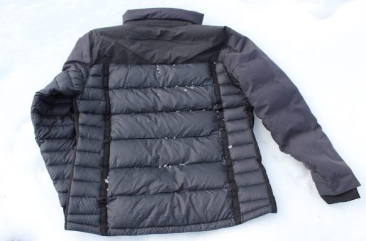 This review photo of the KÜHL Firestorm Down Jacket shows the back of the jacket on snow.
