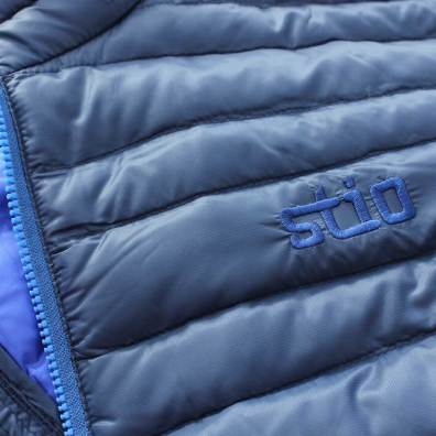 This photo shows the stitched Stio logo on the chest of the Stio Pinion Down Sweater jacket.