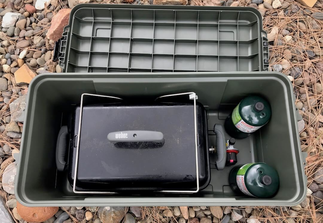 This photo shows the Plano Sportsman's Trunk medium with a Weber Go-Anywere grill inside.