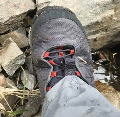 This photo shows a Simms Flyweight Wading Boot from the top while being worn by a fisherman.