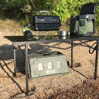 This photo shows the Mountain Summit Gear Heavy-Duty Roll-Top X-Large Camping Table with a grill and cooler on top.