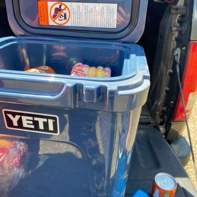 This photo shows the YETI Roadie 24 cooler being used in the back of a pickup truck during a road trip.