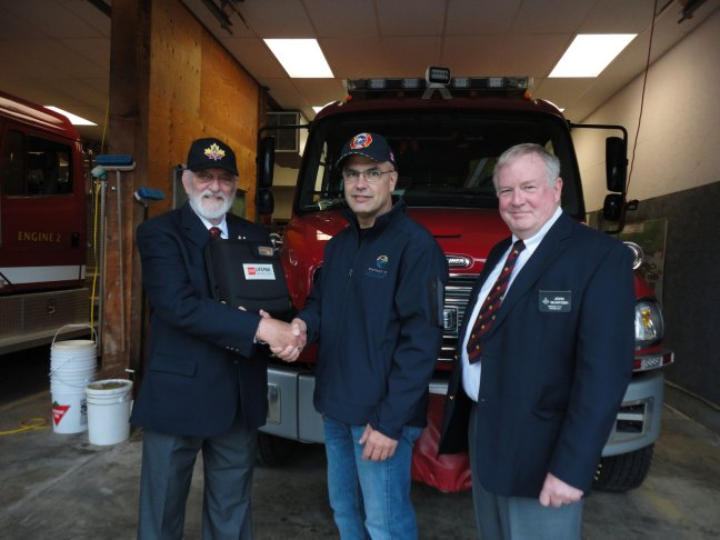 Manoah Lodge No. 141 members Sandy Henry (left) and John McIntosh (right) present a new defibrillator to Ucluelet Fire Chief Rick Geddes, 30 July 2019 (photo: Nora O'Mally - Westerly News)