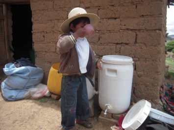 Child in Bolivia drinking from the biosand water filter at his home.