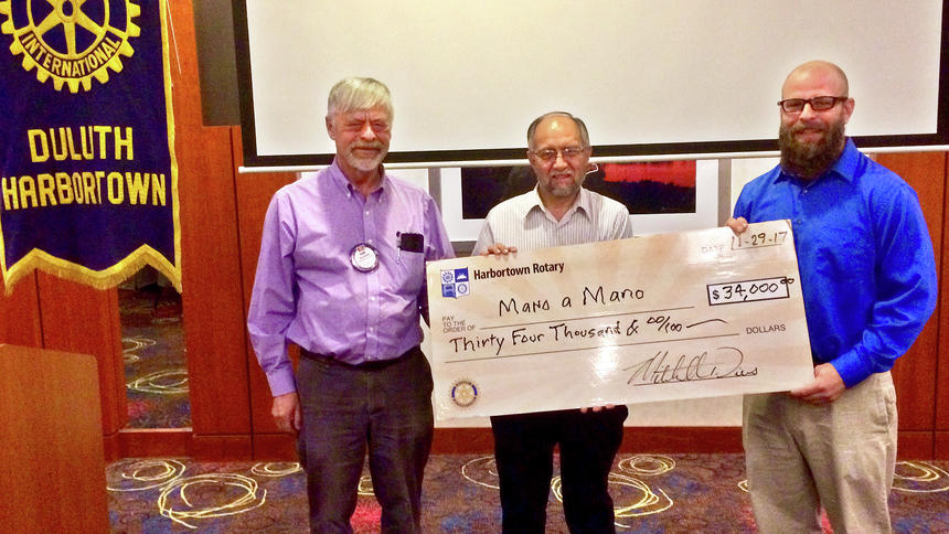 Mano a Mano Co-Founder Segundo Velasquez traveled to Duluth in late 2017 to pick up this Rotary check for the Jatun Mayu clinic project. Photo Credit: Duluth News Tribune