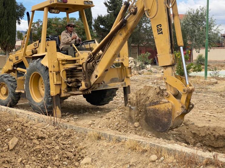 Backhoe in place digging water pond to mix bentonita