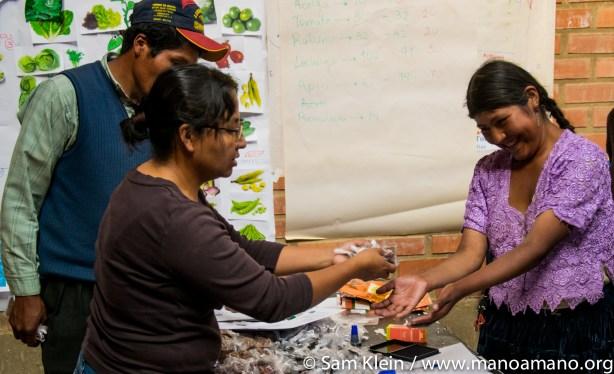 Mano a Mano engineer Camila Yavira gives a farmer seeds for her greenhouse.