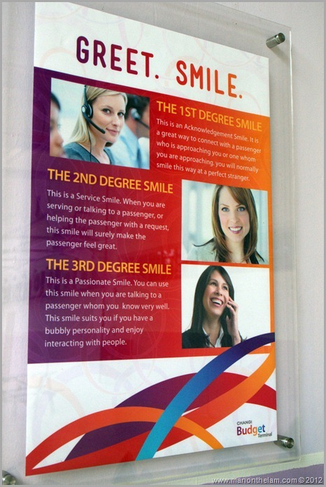 Singapore Changi Airport -- Greet, Smile, Thank program sign -- types of smiles