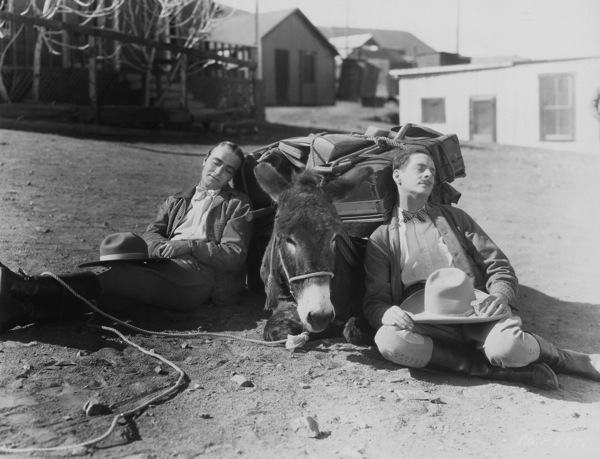 Travellers asleep on street with mule and luggage vintage black and white