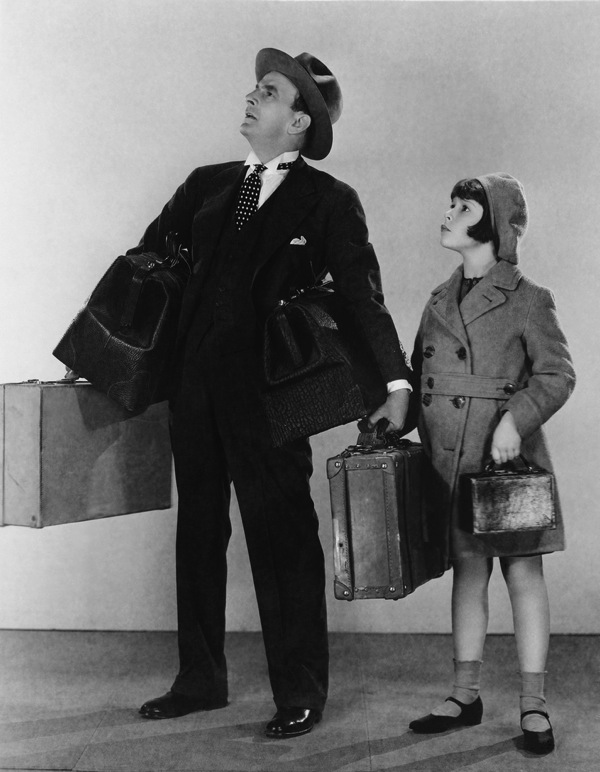Father and daugter with luggage staring into the distance