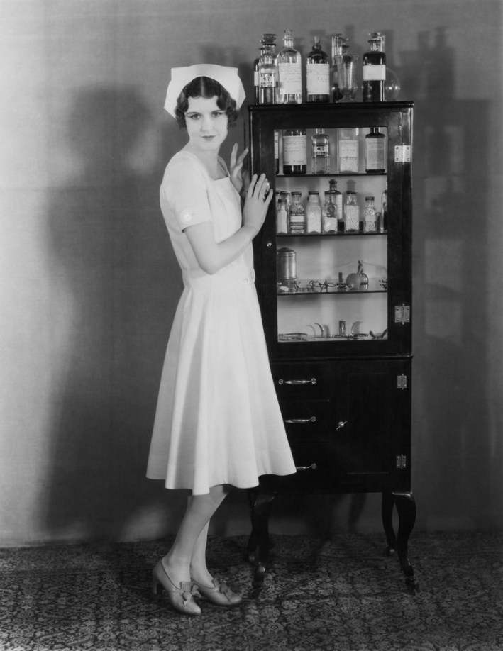 vintage black and white nurse at drug cabinet