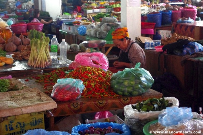 Phonsavan market lady peeking chillies Laos