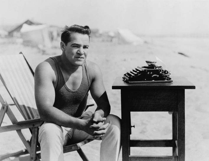 Black and white man on beach with typewriter