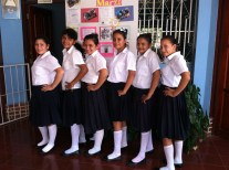 Six girls in school uniforms line up for a photo. They are each turned to their right, and have their left hands on their hips.