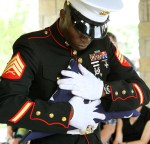 A United States Marine color guard member clutches a folded American flag to be presented to the family at the Memorial service for Richard Latour at Dallas-Fort Worth National Cemetery on Wednesday, June 13, 2012. (Louis DeLuca/The Dallas Morning News)
