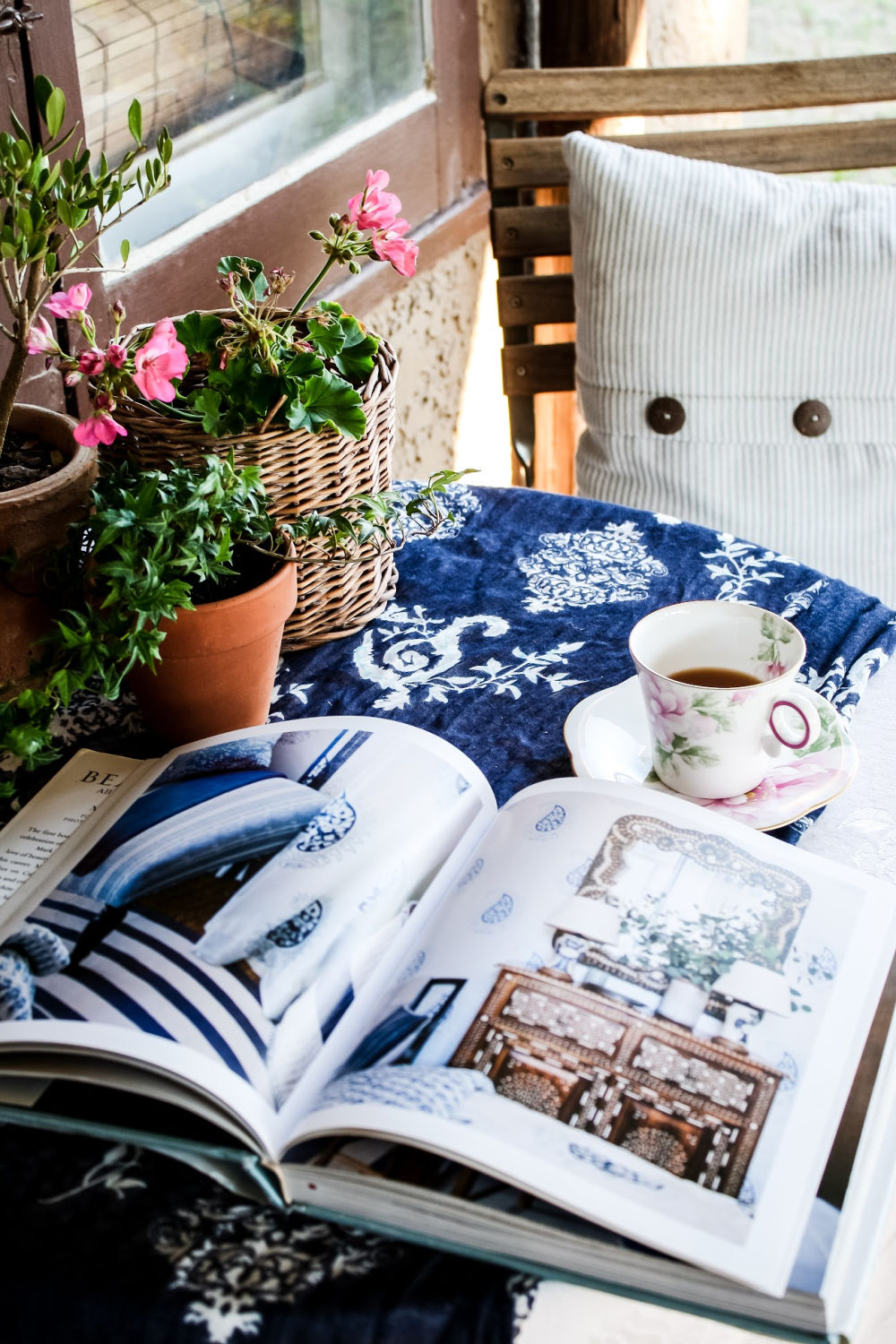 teacup on table with decorating book and flowers