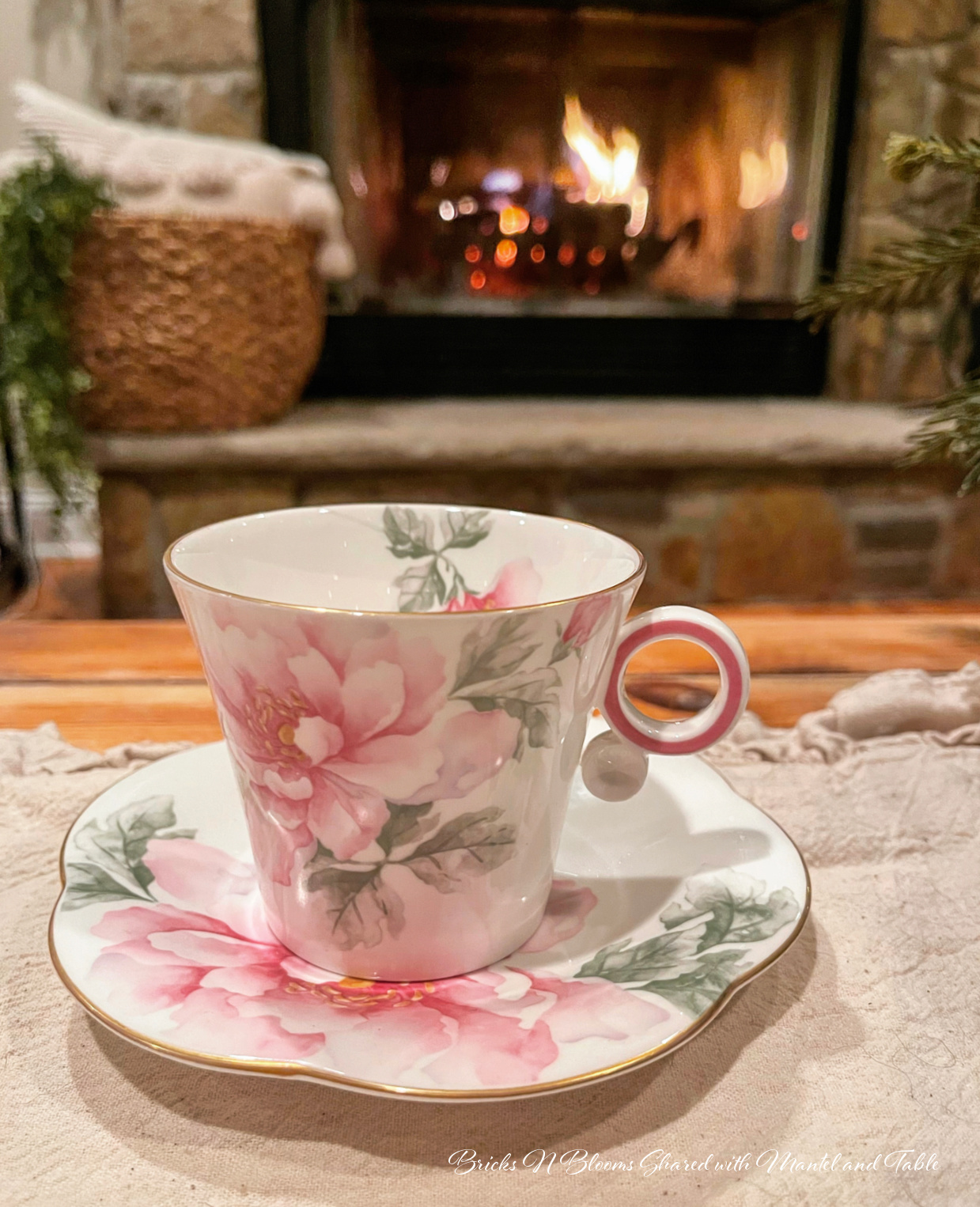Pink flowered teacup in front of a stone hearth with a fire