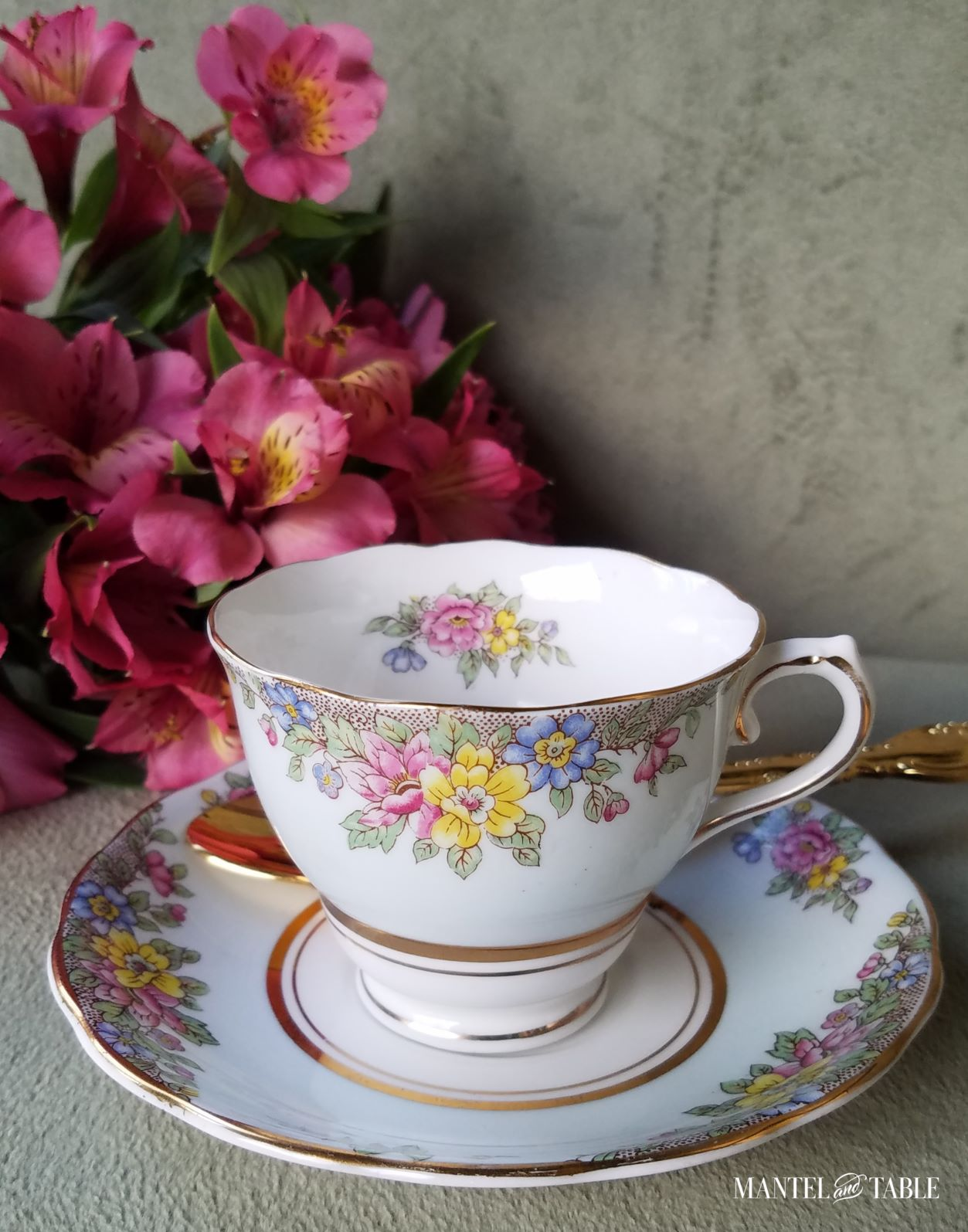 Blue flowered teacup and saucer with gold spoon