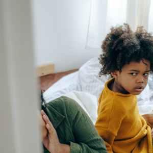 منتوف MANTOUF offended little girl sitting on bed with sibling