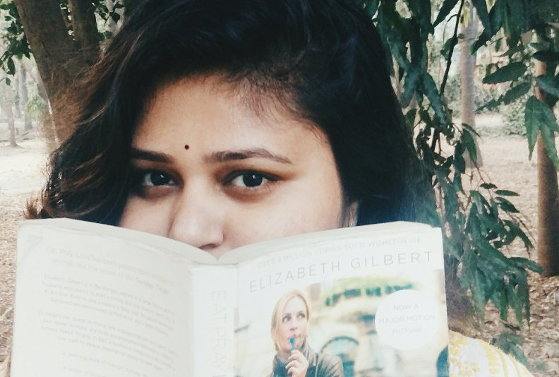 Girl peeking through the book - eat pray love