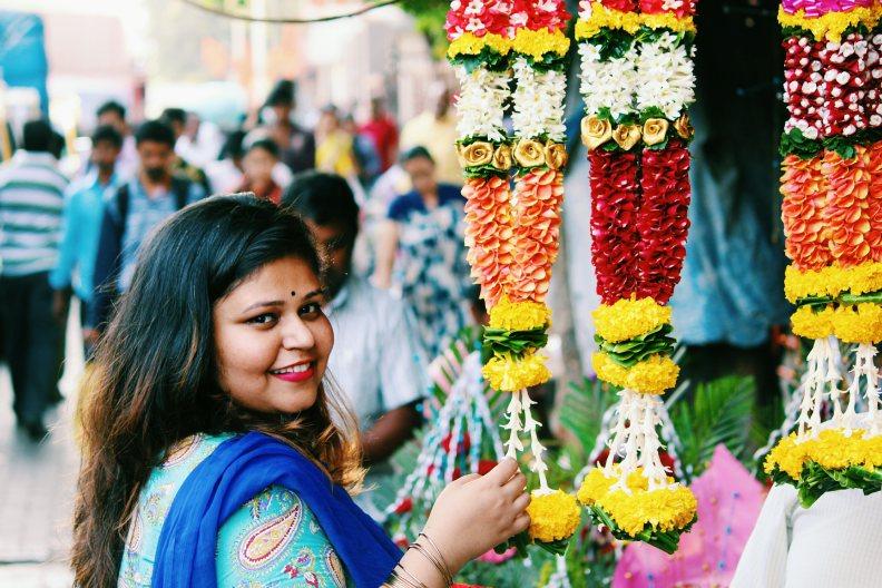 Girl standing near flower garland smiling with touching the garlands in dadar flower market