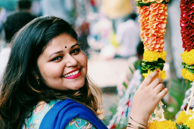 Girl smiling cheerfully with head tilted and touching the flower garland in dadar flower market