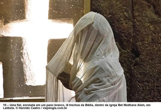 – Uma fiel, enrolada em um pano branco, lê trechos da Bíblia, dentro da igreja Bet Medhane Alem, em Lalibela, Foto Haroldo Castro