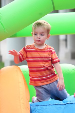 A blow up slide is inflated for children to play around on while parents listen to music by several performers.