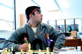 """Nathaniel Smith (12) plays chess dressed as a """"Chick Magnet"""" for Red/White Week. Photo by Jackie Leachman"""