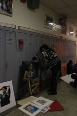 Charlena Vaughn (12) carefully places her artwork against the lockers in the VA wing.