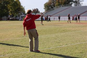 Coach Sam Coryell (11) adjusts the players on the field.
