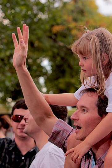 A father lifts his daughter up to see over the crowd.