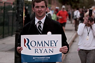 A Romney supporter walks on the sidewalk along the Occupy protesters, showing his support for the Romney Ryan campaign.
