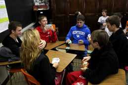 A group of students gather to play a card game after stressful day of testing.