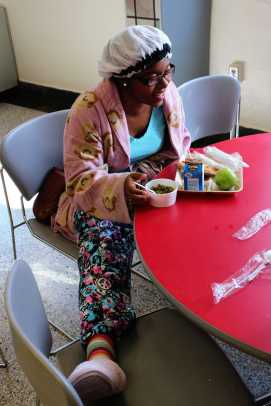 Deja Bowen (11) lounges in the lunch room eating with her friends.