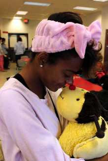 Destiny Witherspoon (11) cuddles her pillow pet whole waiting in line for lunch.