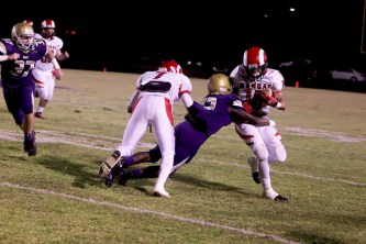Dishan Romine (12) runs through a Male defender while carrying the ball.
