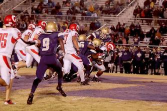 Tyron Horton (10) runs throw and carries several Male players.