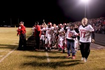 The football players on the sideline cheer as the final seconds tick down.