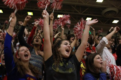 Riley Morrissey (11) and other juniors express their school spirit by cheering and waving pom-poms. Photo by Meg Shanks