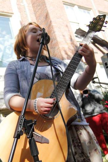 Clare Hagan (11) sings and plays acoustic guitar for the crowd of Ramstock listeners.