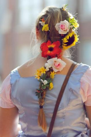 "A student has flowers pinned in her hair for her portrayal of Rapunzel from recent Disney movie, ""Tangled."""