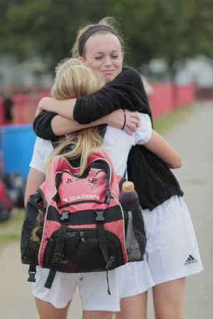 Jordyn Barnes (11, #17) embraces Kylie King (12, #13), sad that her senior friend will soon be leaving her.