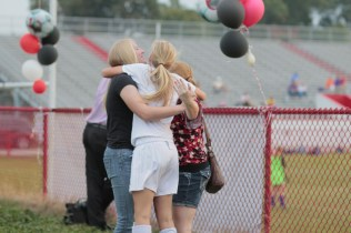 Kylie King (12, #13) embraces her older sisters Kelsey King and Kayla King, both Manual graduates. Kylie did not know they were coming and is overwhelmingly happy by the surprise.